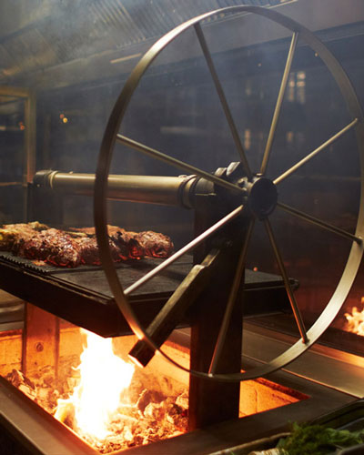 Locally-raised meat cooks over an open grill.